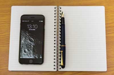 iPhoneとノートの写真
